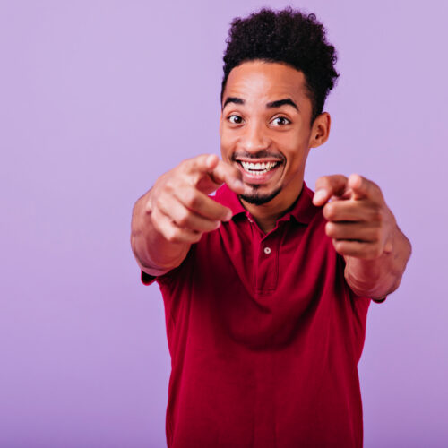 Inspired african guy pointing finger to camera. Studio shot of laughing positive black man smiling on purple background.